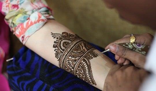 applying mehendi on brides hands-bigindianwedding