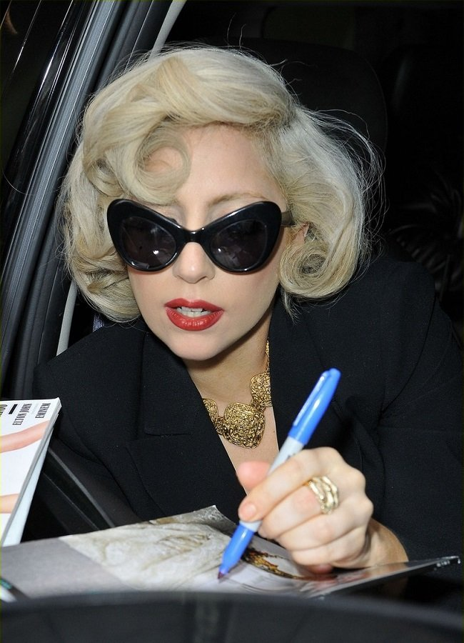 Lady Gaga, wearing cat eye sunglasses and a revealing top, channels her inner Marilyn Monroe while leaving her hotel